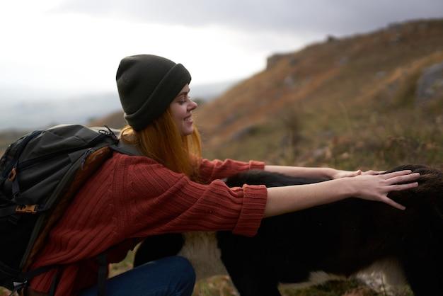 Веселая туристка женщина играет с собакой природа пейзаж горы дружба