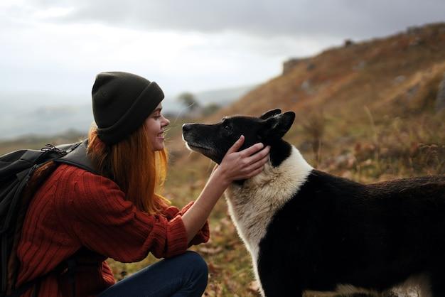 Веселая туристка женщина играет с собакой природа пейзаж горы