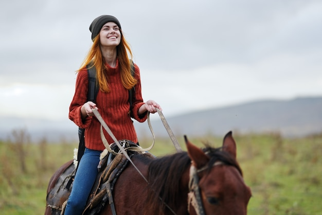 山で馬に乗る陽気な女性ハイカー