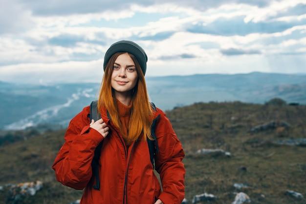 山の中を歩く陽気な女性ハイカーアクティブな休暇旅行。高品質の写真
