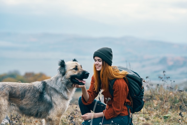 陽気な女性ハイカーが山の風景の中の自然に犬を散歩させる