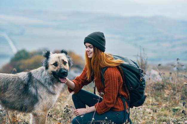 陽気な女性ハイカーは、山の風景の中の自然の上で犬を散歩します