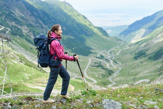 Веселая женщина турист с рюкзаком, наслаждаясь красивым пейзажем гор