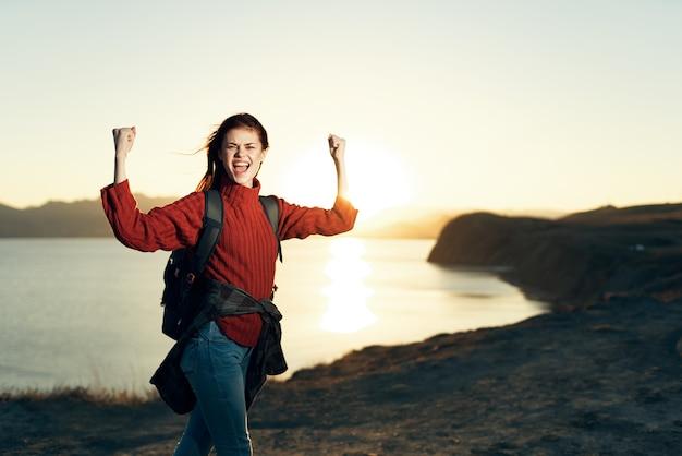 自由の風景を上げた手でバックパックと陽気な女性ハイカー