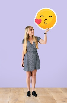 Cheerful woman holding a kissing emoticon