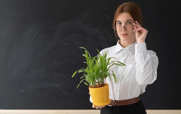 Веселая женщина, держащая растение возле доски