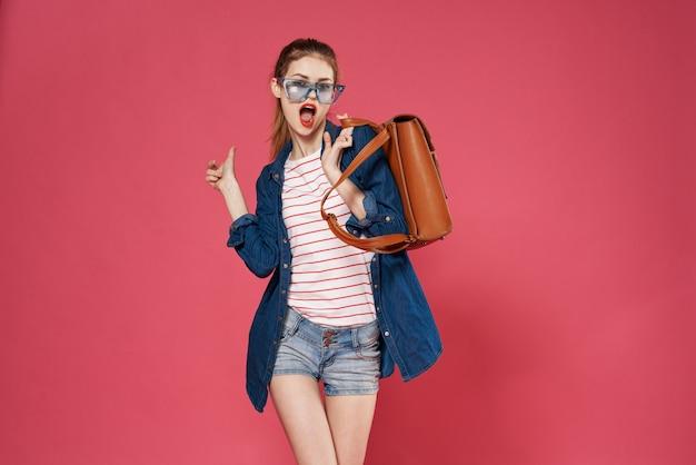 赤い背景にバックパックを保持している陽気な女性