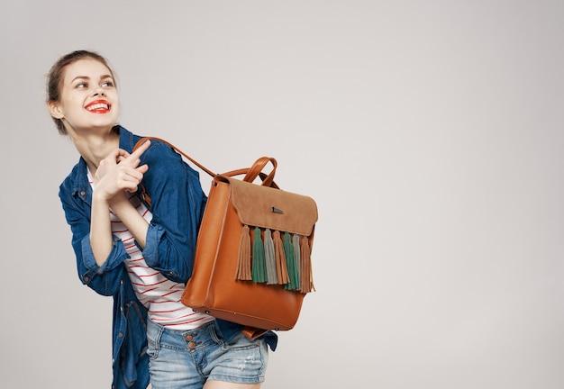白い背景の上のバックパックを保持している陽気な女性