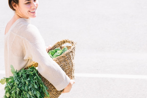 Cheerful woman holding basket with vegetables