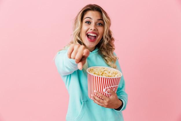 Веселая женщина держит ведро с попкорном и смотрит в камеру, изолированную над розовой стеной
