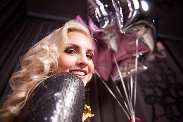 Donna allegra che tiene un mazzo di palloncini al night club