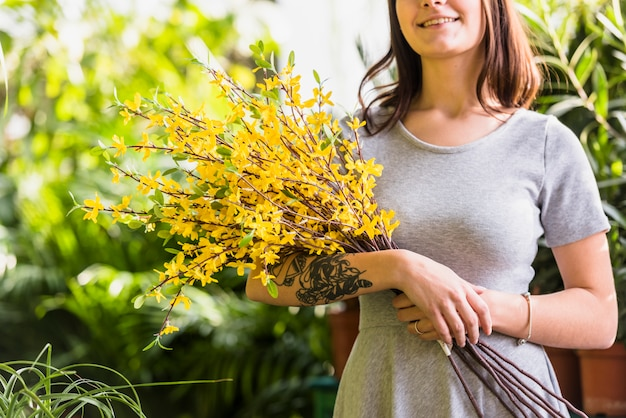 Cheerful woman holding bunch of plant twigs