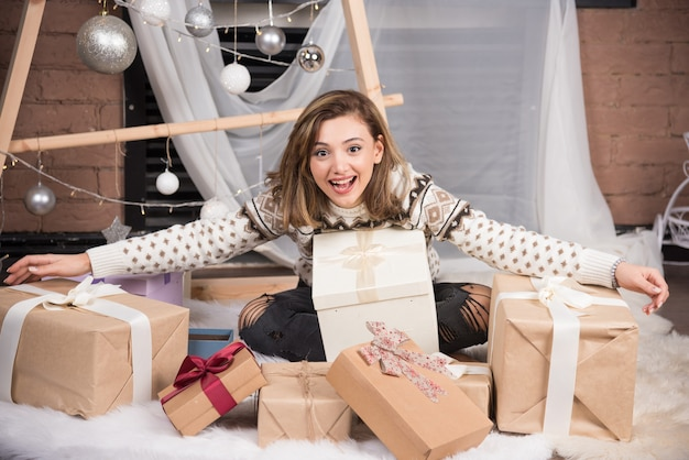 Cheerful woman holding a christmas gift in living room.