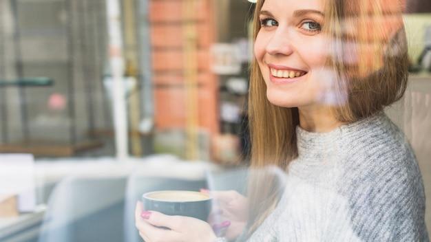 コーヒーのカップを持っている陽気な女性