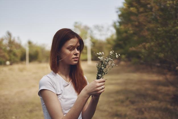 Cheerful woman holding flowers sun freedom journey
