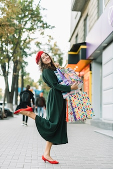 Cheerful woman holding full shopping bags on street