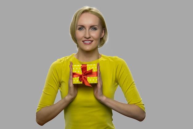 회색 바탕에 선물 상자를 들고 쾌활 한 여자입니다. 선물 상자 카메라보고 꽤 웃는 여자.