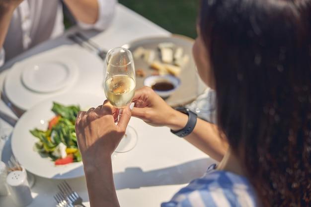 식탁에 앉아있는 동안 손에 샴페인 잔을 들고 쾌활한 여자