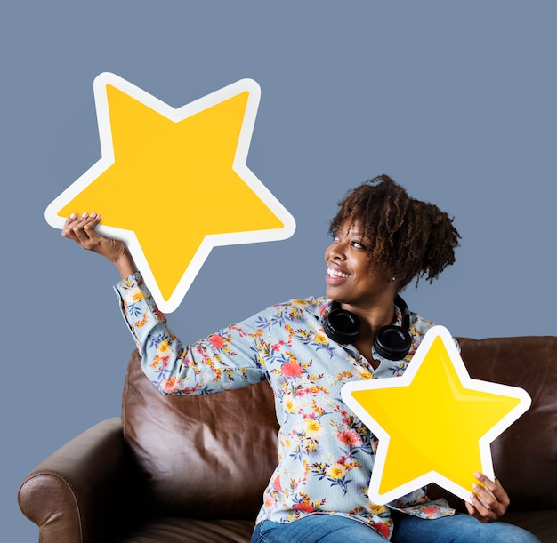 Cheerful woman holding golden stars icons