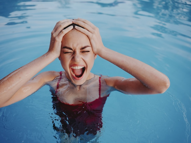 Cheerful woman holding her head in the pool swimming leisure