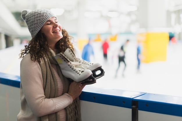 Cheerful woman holding ice skates
