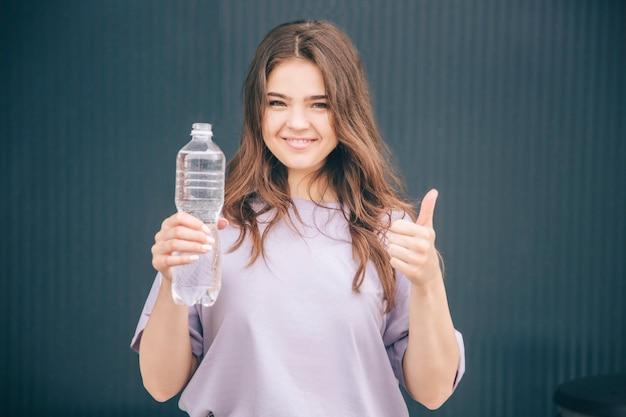 プラスチック製の水ボトルを押しながら大きな親指を現して陽気な女性