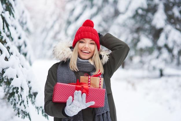 크리스마스 선물의 스택을 들고 쾌활 한 여자
