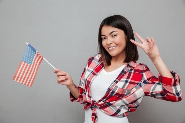 Donna allegra che tiene la bandiera di usa sopra la parete grigia