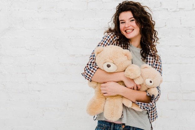 Cheerful woman hugging plush toys