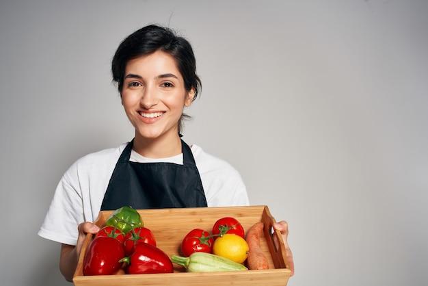 검은 앞치마 야채 가사 요리에 쾌활 한 여자입니다. 고품질 사진