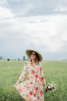 フィールドで花柄のドレスを着た陽気な女性