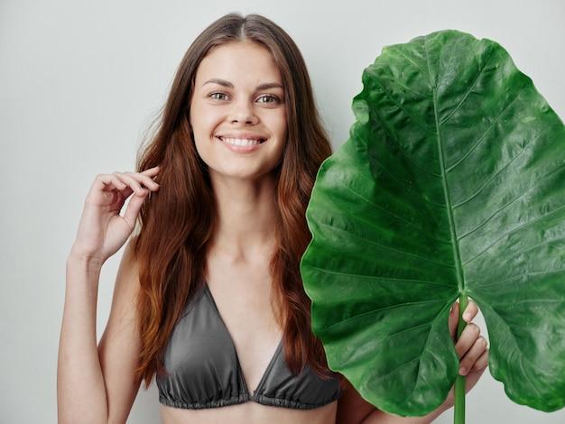 彼女の髪を保持している彼女の手に緑の葉を持つ灰色の水着で陽気な女性