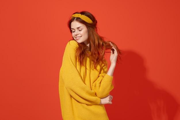 黄色の背景に彼女の手で緑のセーターのジェスチャーで陽気な女性