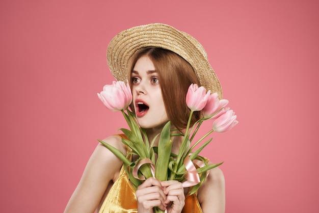 花の帽子の花束で陽気な女性3月8日の休日の女性の日