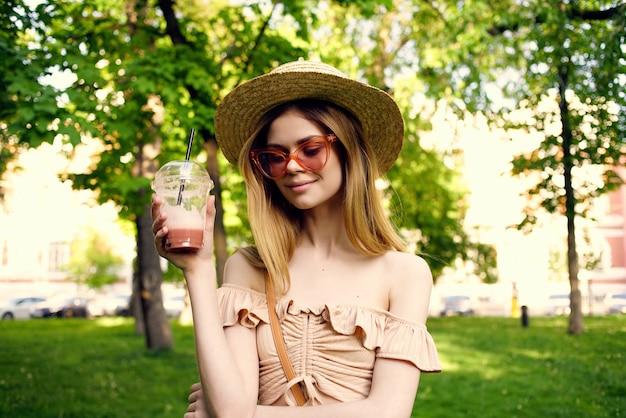 공원 음료 휴식 라이프 스타일에서 모자에 쾌활 한 여자