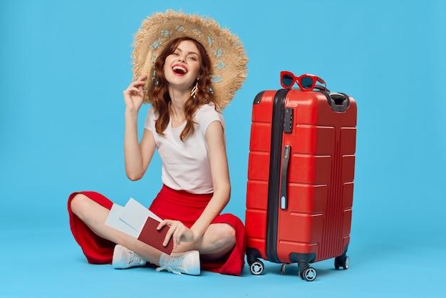 모자를 쓴 쾌활한 여성이 여행 가방을 들고 바닥에 앉아 있다