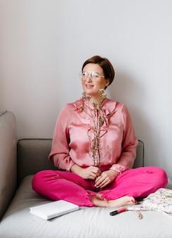 ワックスフラワーを保持しているピンクのシャツの陽気な女性