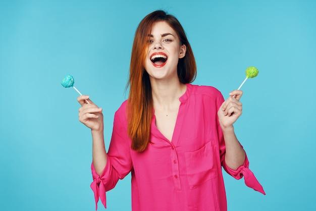 手の感情の贅沢でピンクのシャツロリポップの陽気な女性