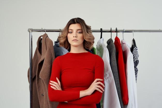 Жизнерадостная женщина в красной куртке возле шкафа изолированного фона. фото высокого качества