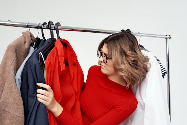 옷장 소매 고립 된 배경 근처 빨간 재킷에 쾌활 한 여자. 고품질 사진