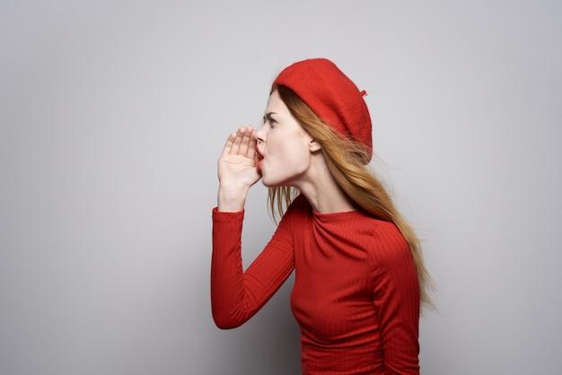 赤いセーター化粧品感情孤立した背景の陽気な女性。高品質の写真