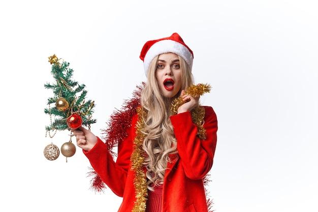彼女の手でクリスマスツリーを保持しているサンタの衣装で陽気な女性