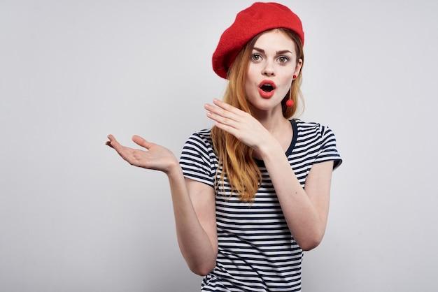 ストライプのtシャツの赤い唇のジェスチャーで陽気な女性と彼の手は分離された背景