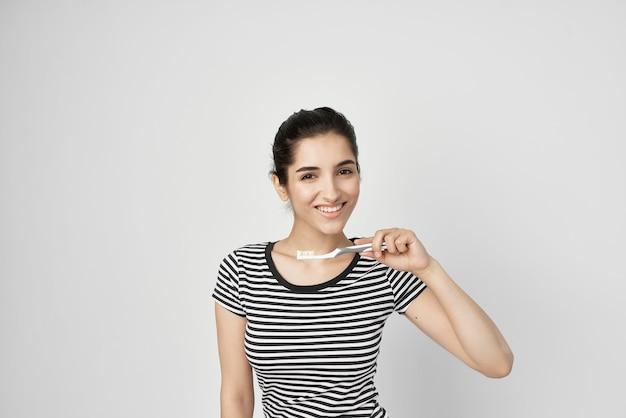 手で隔離された背景の縞模様のtシャツの歯ブラシで陽気な女性