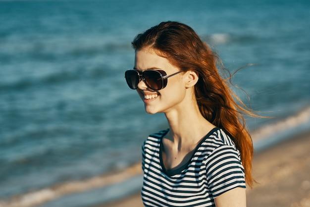 Tシャツとメガネの陽気な女性が山の海岸で休んでいます