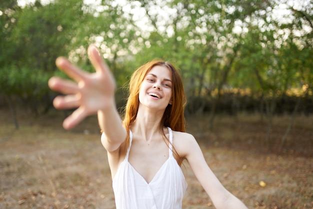 フィールド自然感情の自由の白いドレスを着た陽気な女性