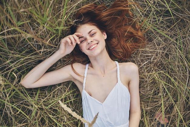 白いドレスを着た陽気な女性は、芝生の上に横たわっています。