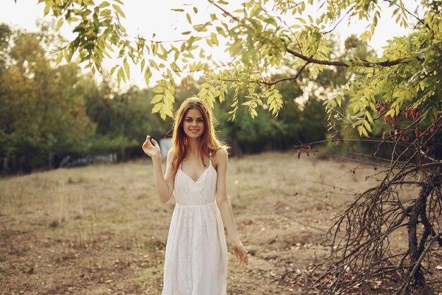 야외 필드 산책에서 흰 드레스에 쾌활 한 여자