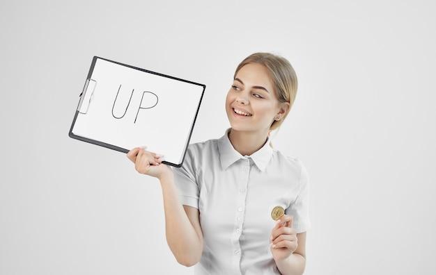 白いシャツを着た陽気な女性は、上向きの暗号通貨ビットコインインターネットフィンランドの碑文のあるフォルダーを保持しています