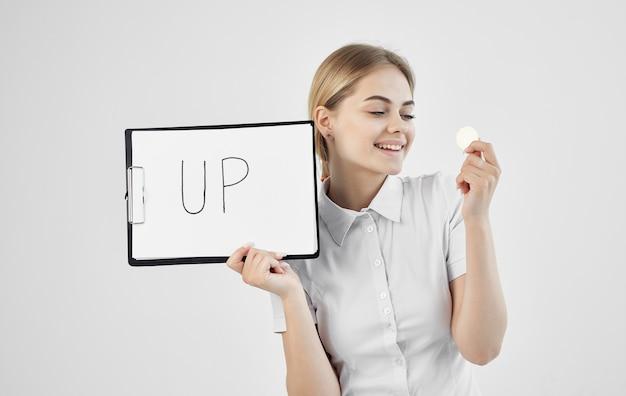 白いシャツを着た陽気な女性は、上向きの暗号通貨ビットコインインターネットフィンランドの碑文が入ったフォルダーを持っています。